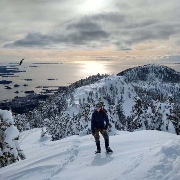 A hiker pauses in front of the Gavan Hill Trail, over a scenic overlook of Sitka Sound